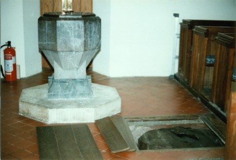 A pagan standing stone in the floor by a Christian font